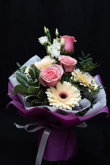 Lindo buquê com rosas e gerberas em uma parede preta.