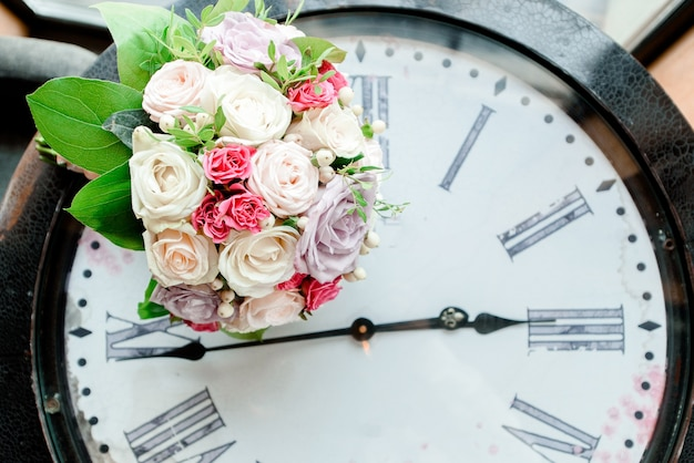 Lindo buquê de casamento ao longo de um relógio vintage.