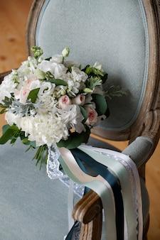 Lindo buquê de casamento rico em uma cadeira de madeira luxuosa