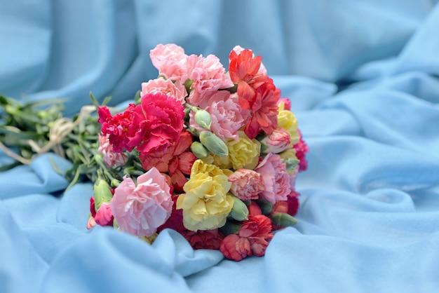 Lindo buquê de cravo de flores coloridas em um tecido azul