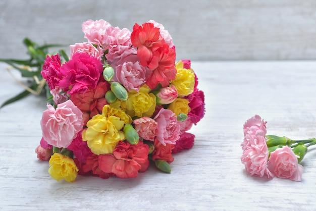 Lindo buquê de cravo de flores coloridas em uma mesa branca