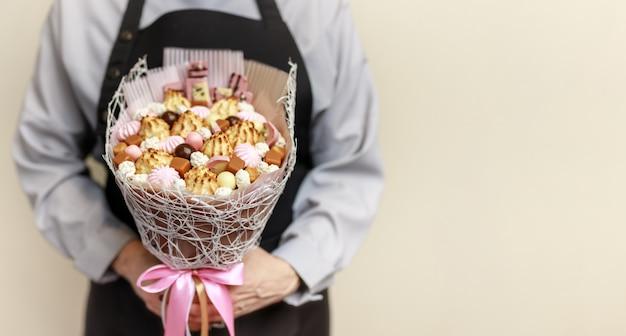 Lindo buquê de doces, marshmallows e biscoitos nas mãos de um confeiteiro