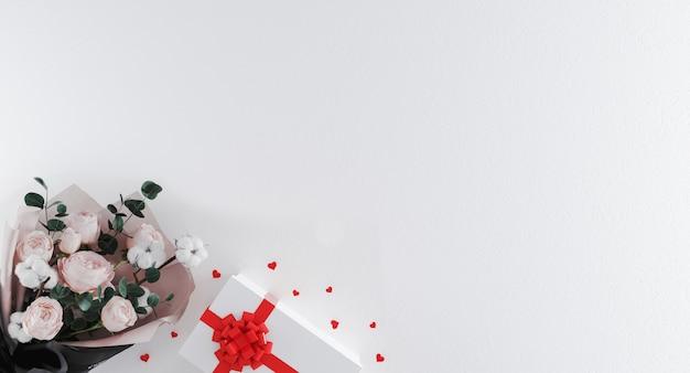 Lindo buquê de flores com caixa de presente branca com fita vermelha e confetes em forma de coração no fundo branco. dia dos namorados