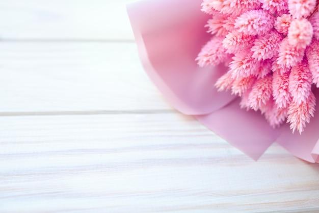 Lindo buquê de flores cor de rosa secas em um fundo branco de madeira