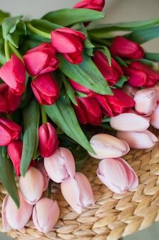 Lindo buquê de flores de tulipas vermelhas e rosa primavera no tapete da mesa de palha