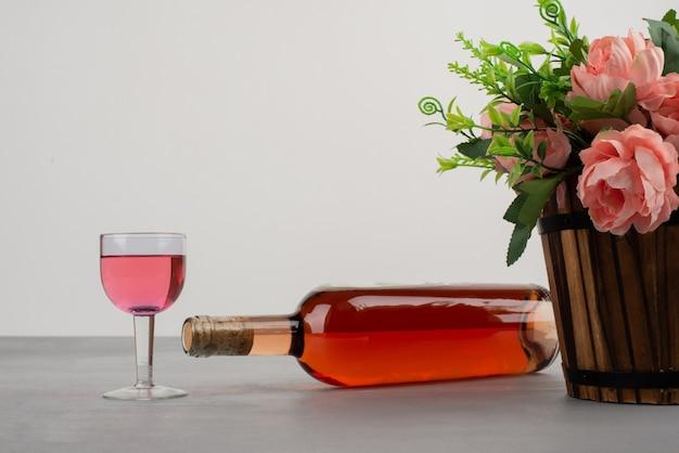 Lindo buquê de flores e garrafa de vinho rosé na mesa cinza.