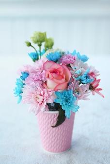Lindo buquê de flores em um copo rosa na mesa.