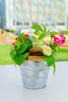 Lindo buquê de flores em um pequeno balde de metal. decoração de interiores e jardins.