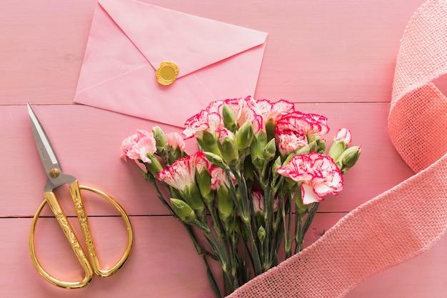 Lindo buquê de flores frescas perto de fita e envelope