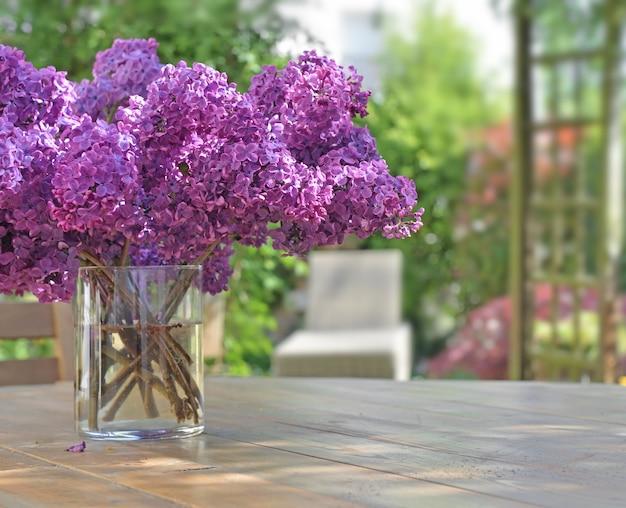 Lindo buquê de flores lilases roxas em uma mesa de madeira no jardim
