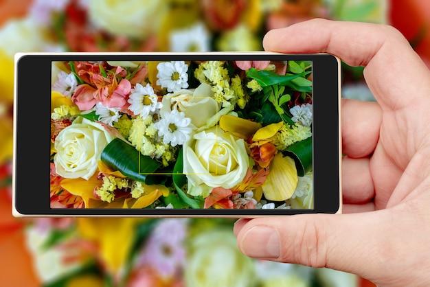 Lindo buquê de flores na tela do smartphone. fundo natural floral decorativo.