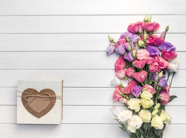 Lindo buquê de flores rosa, roxo, amarelo eustoma e caixa de presente artesanal em fundo branco de madeira. copiar espaço, vista superior
