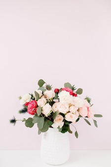 Lindo buquê de flores rosas bombásticas, eríngio azul, galhos de eucalipto em vaso na parede rosa