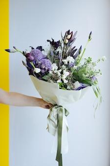 Lindo buquê de flores roxas nas mãos no fundo da parede cinza, vista lateral de entrega de loja de flores moderna