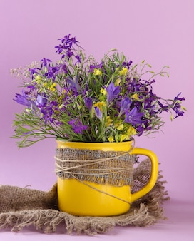 Lindo buquê de flores silvestres na xícara em fundo roxo