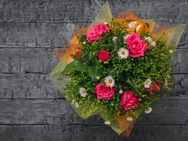 Lindo buquê de flores vermelhas e brancas com plantas verdes em uma mesa de madeira preta