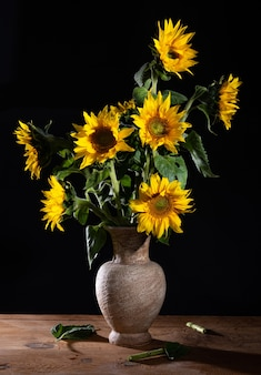 Lindo buquê de girassóis em um vaso sobre uma mesa de madeira.