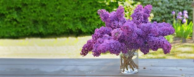Lindo buquê de lilás roxo em uma mesa de madeira no jardim com vista panorâmica