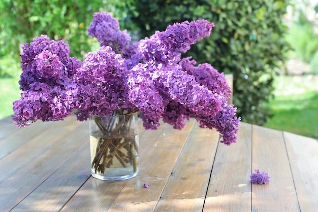 Lindo buquê de lilás roxo em uma mesa de madeira no jardim