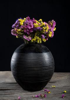 Lindo buquê de limônio em um vaso sobre uma mesa de madeira.