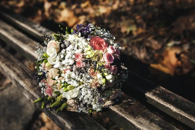 Lindo buquê de noiva deitado em um banco do parque, casamento no outono