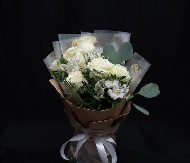 Lindo buquê de rosas brancas, alstroemeria e lisianthus em embalagens kraft em uma parede preta.