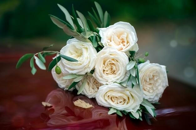 Lindo buquê de rosas brancas no capô vermelho de um carro. fechar-se. fundo, textura. tingimento