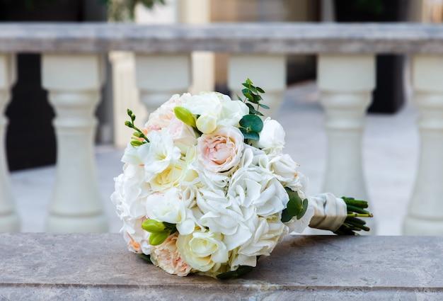 Lindo buquê de rosas e eustoma em um corrimão de mármore vintage