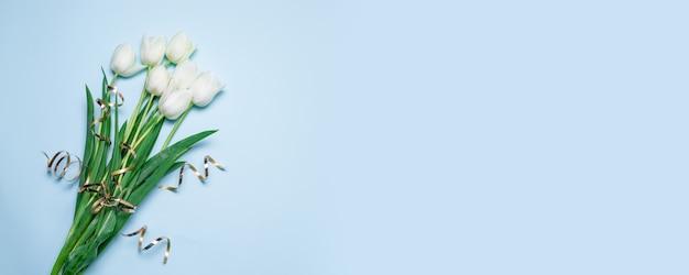 Lindo buquê de tulipas brancas sobre um fundo azul com espaço para seu banner de texto