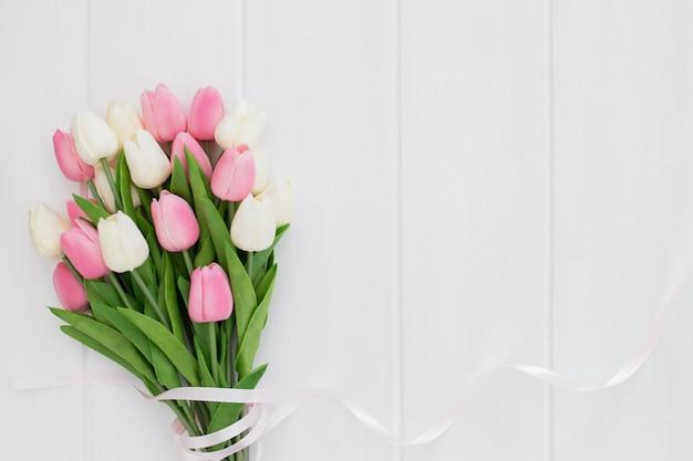 Lindo buquê de tulipas cor de rosa e brancas em fundo branco de madeira