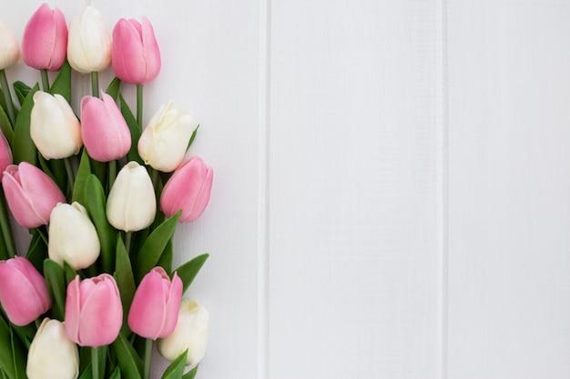 Lindo buquê de tulipas em fundo branco de madeira com copyspace à direita