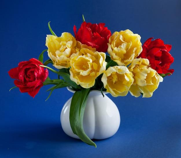 Lindo buquê de tulipas frescas vermelhas e amarelas em um vaso branco sobre um fundo azul. close-up, foco seletivo