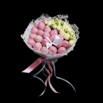 Lindo buquê delicado, composto por morangos em chocolate rosa e rosas brancas fica em um vaso de vidro