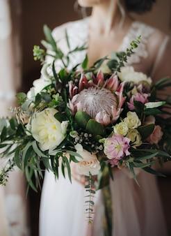 Lindo buquê e noiva em um vestido de noiva branco meio retrato