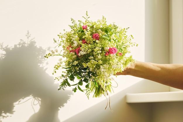 Lindo buquê fresco de flores de lírio do vale, rosa rosa, ramos verdes na mão da mulher