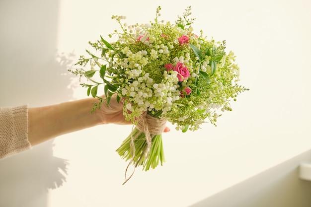 Lindo buquê fresco de flores de lírio do vale, rosa rosa,