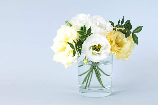 Lindo buquê fresco e moderno de eustoma em um vaso de vidro transparente com espaço de cópia