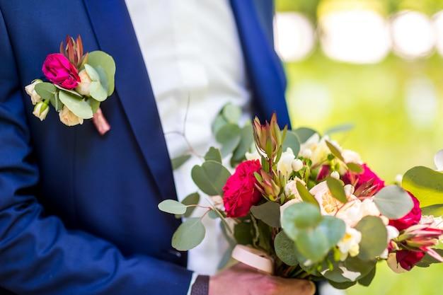 Lindo buquê misturado flores nas mãos de um noivo de terno azul.