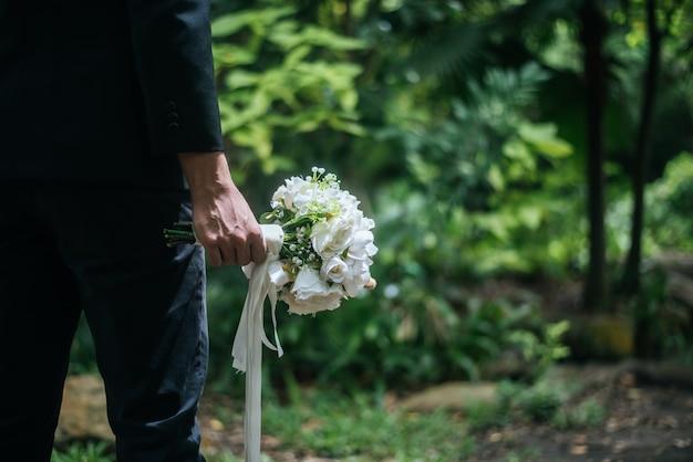 Lindo buquê nas mãos do noivo para a noiva.