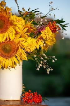 Lindo buquê outonal de flores de girassol amarelas brilhantes em um vaso branco na mesa de madeira na zona rural. outono natureza morta com flores no jardim.
