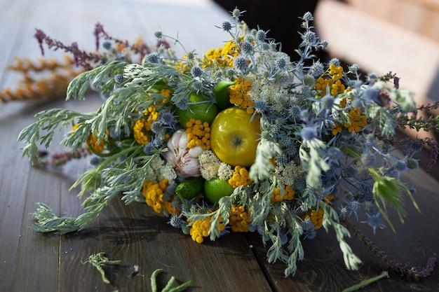 Lindo buquê perfumado de flores silvestres mentira sobre uma mesa de madeira, close-up