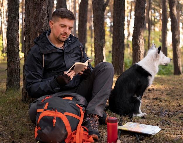 Lindo cachorro preto e branco e homem lendo