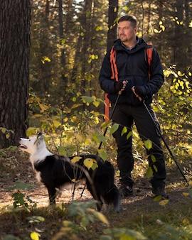 Lindo cachorro preto e branco e homem na floresta