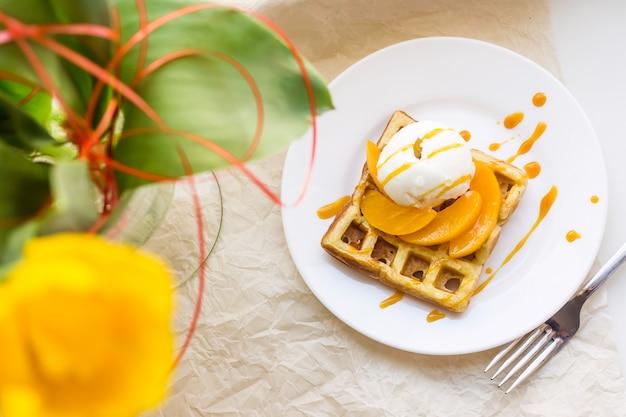 Lindo café da manhã waffle belga festiva ao lado de uma tulipa amarela