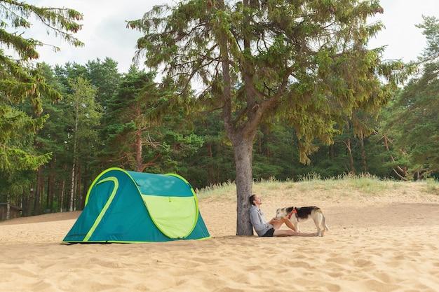 Lindo cão pastor com o dono sentado perto de uma barraca sob uma árvore em uma praia arenosa