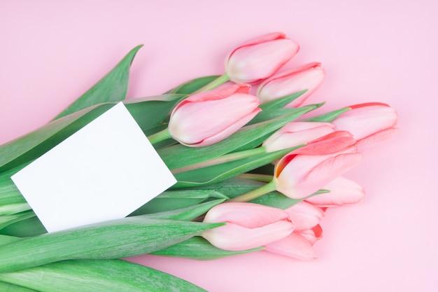 Lindo cartão de felicitações com flores de tulipas em fundo rosa