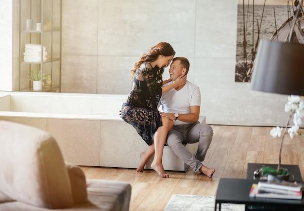 Lindo casal abraçando e olhando um ao outro em casa