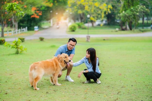 Lindo casal acariciando o cão golden retriever no jardim
