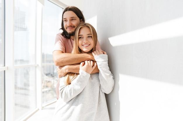 Lindo casal adorável parado na sala de estar perto da janela, se abraçando