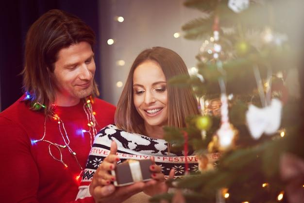 Lindo casal adulto com presente sobre a árvore de natal